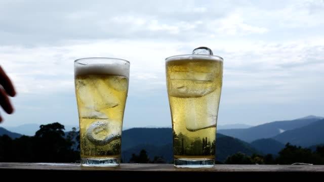 自然な背景でビールを飲んだり、眼鏡をかけたりして手をつないで - グラス点の映像素材/bロール