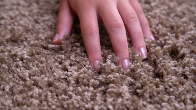 Close up of hand touching soft carpet. Gentle and fluffy carpet between finger