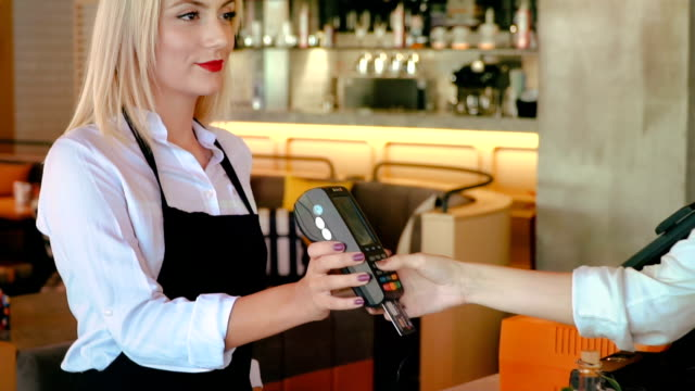 Close up of hand using credit card swiping machine to pay. Woman entering credit card code in swipe machine.