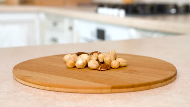 Close up of handful of different nuts. Rotating camera with white kitchen on the background. Dolly-shot.