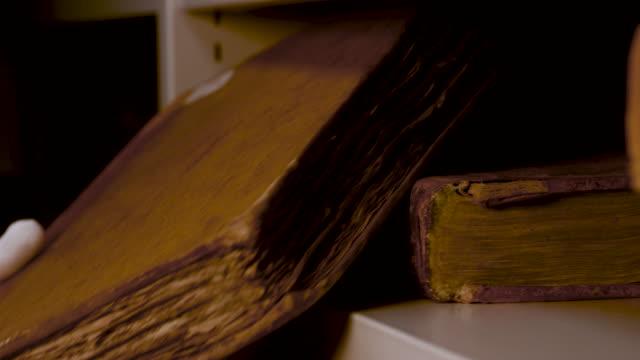 古いアンティークの本を棚に置く白い手袋で手を閉じて非常に慎重に。ストック映像。ストレージ内の黄色のページを持つ古代の本 ビデオ
