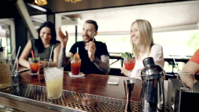 Close up of hands of a bartender doing fresh cocktail. Man at bar counter preparing beverages for company sitting opposite him. Young hipster expressing his happiness to two girlfriends video