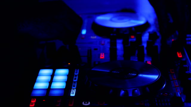 close up of hands of a dj playing on a digital controller in a dark nightclub - giradischi video stock e b–roll