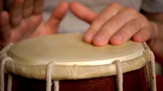vidéos et rushes de gros plan des mains d'un homme jouant un tambour. ralenti. - instrument à percussion