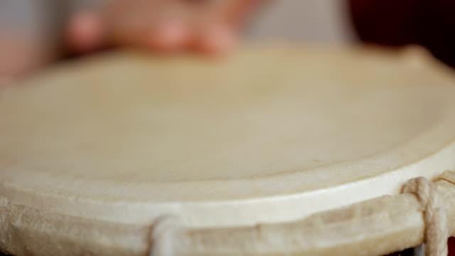 vidéos et rushes de gros plan des mains d'un homme jouant du tambour. - instrument à percussion