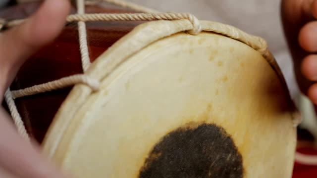 vidéos et rushes de gros plan des mains d'un homme jouant un tambour. - instrument à percussion