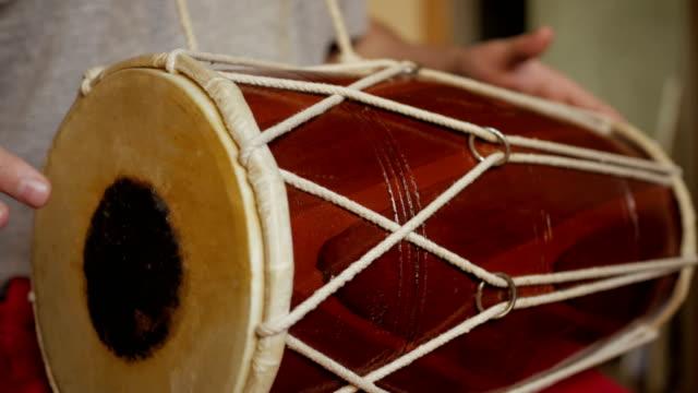 vidéos et rushes de fermez-vous vers le haut des mains d'un homme jouant un tambour. - instrument à percussion