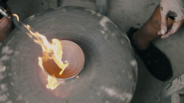 vídeos de stock, filmes e b-roll de close-up das mãos de um oleiro, criando uma xícara na roda círculo enquanto estiver usando fogo spray espuma-stock vídeo - cerâmica artesanato