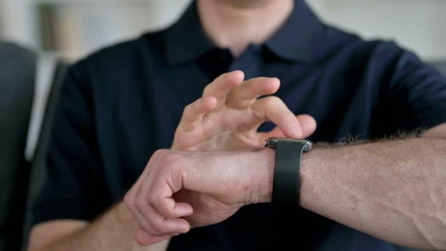close up of hands of man using smart watch - staw człowieka filmów i materiałów b-roll