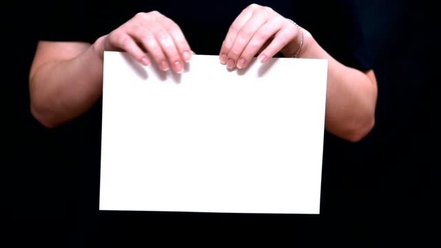 vídeos y material grabado en eventos de stock de cerca de las manos con una hoja de papel sobre un fondo de color. manos rasgan una hoja de papel blanco a través de. - ripped paper