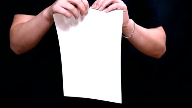 vídeos y material grabado en eventos de stock de cerca de las manos con una hoja de papel. rasga una hoja de papel blanco en longitud. - ripped paper