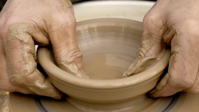 vídeos de stock, filmes e b-roll de feche de mãos trabalhando argila em potter. - cerâmica artesanato