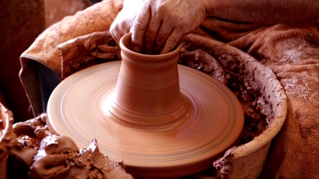 Close up of hands working on pottery wheel