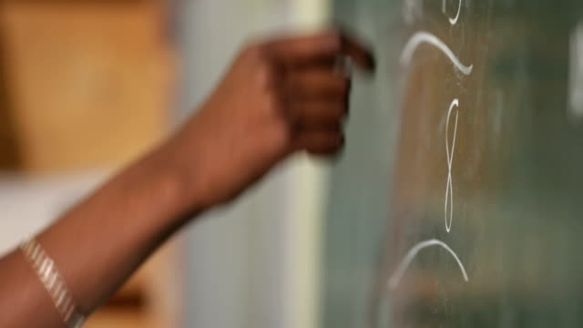 Close up of hands writing on cahlk board A close up of a schoolboys hands as he writes with chalk on a board, working out a mathematics equation. blackboard visual aid stock videos & royalty-free footage