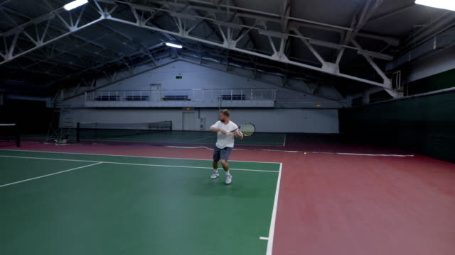 Close up of handsome professional tennis player in white shirt, grey shorts and shoes training at indoor court with equipment. Sportsman serving and returning balls with racket in recreation area video