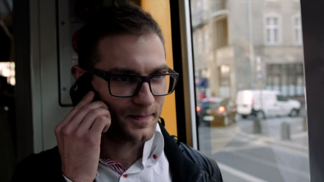 クローズアップのハンサムな若い男は電話で話しているトラムが便利です。 - クラシファイド広告点の映像素材/bロール
