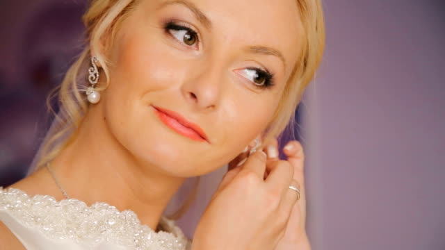 Close up of happy bride wears beautiful earrings video