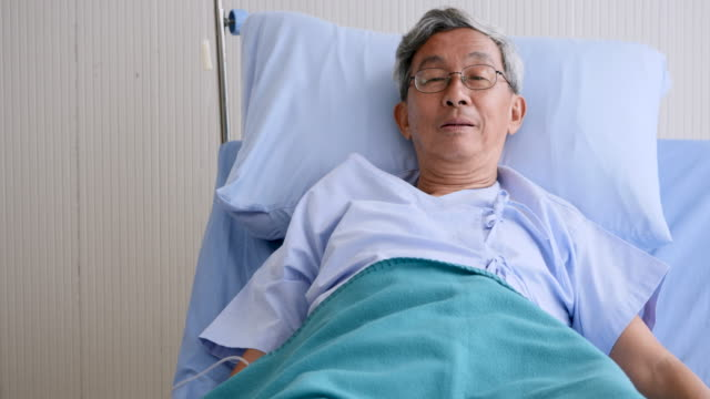 Close up of happy elderly man on patient bed at hospital video