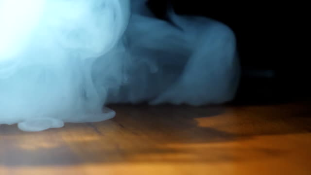 Close up of heavy smoke from an electronic cigarette or hookah appearing on the surface of table. Beautiful club of milk steam from the vape spreading on the wooden desk. Black background. Low view