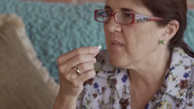Close up of Hispanic mature woman taking medicine at home Close up of Hispanic mature woman taking medicine at home painkiller stock videos & royalty-free footage