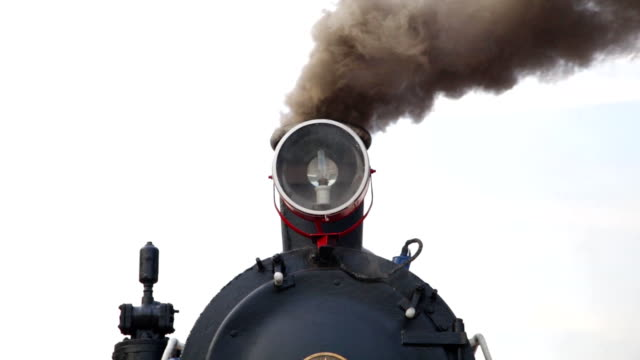 Close up of historic retro steam train with smoke going right Close up of historic retro steam train with smoke going right railroad station platform stock videos & royalty-free footage