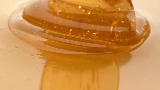 vídeos de stock e filmes b-roll de close up of honey pouring in slow motion - mel