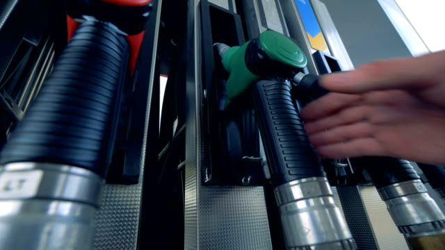 close up of human hand putting out a green fuel nozzle. gasoline fuel, gas station concept. - заправляться стоковые видео и кадры b-roll