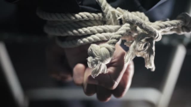 Close up of human hands tied with white colored rope and sitting on a metal chair.