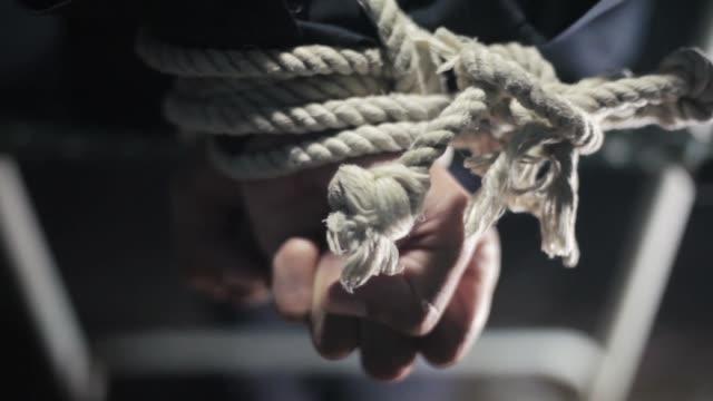vídeos y material grabado en eventos de stock de cierre de las manos humanas atadas con cuerda de color blanco y sentado sentado sobre una silla de metal. - amarrado