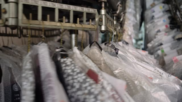 Close up of industrial conveyor belt at an industrial laundry service with clothes hanging on it