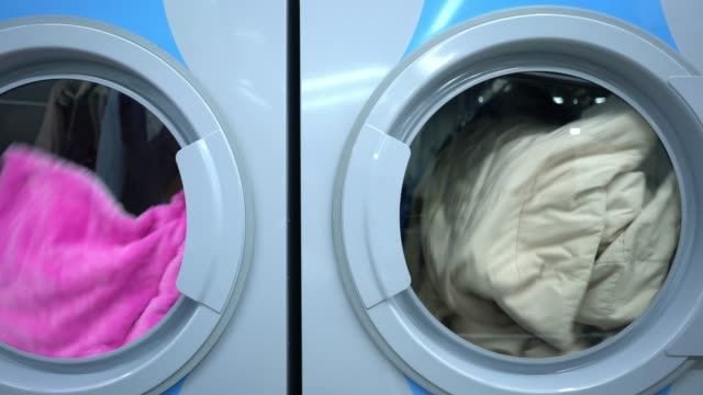 Close up of industrial washing machines and dryer machines at a laundry service