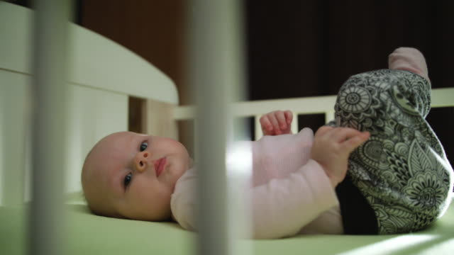 Close up of Infant Baby Laying in Crib Legs Up Motion video