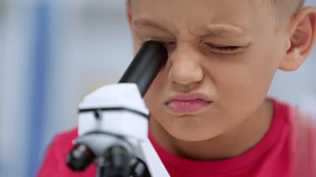 primo passo di bambino guardando attraverso il microscopio - solo bambini maschi video stock e b–roll