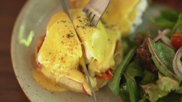 närbild av kniv och gaffel skär pocherat ägg och avokado smörgås - frying pan bildbanksvideor och videomaterial från bakom kulisserna
