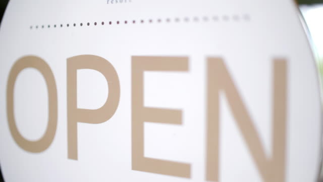 Close up of label sign from close to open and welcoming customers at restaurant