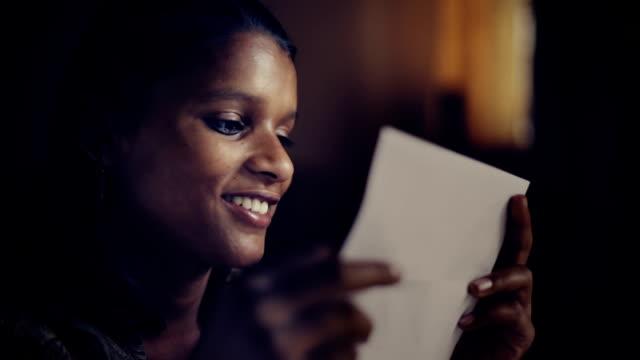 vídeos de stock e filmes b-roll de close up of late teen girl reading letter and smiling. - correio