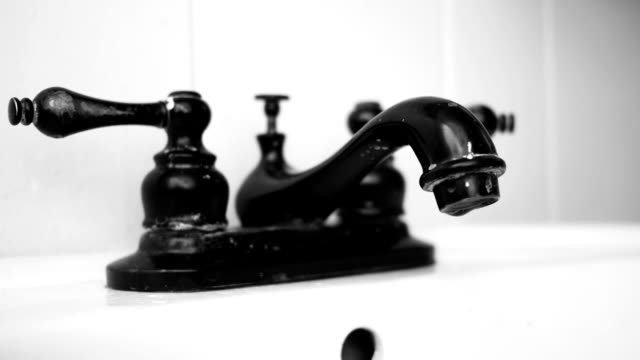 Close up of leaking antique Victorian faucet in bathroom - Black White Version video