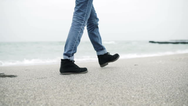 Close up of legs of a young hipster man or woman in mustard trousers and black stylish shoes walking alone on the beach. video