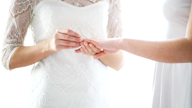 close up of lesbian couple hands with wedding ring people, homosexuality, gay, same-sex marriage and love concept - close up of happy lesbian couple hands putting wedding ring on finger lesbian stock videos & royalty-free footage