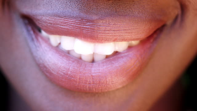 close up of lips and teeth of  a smiling black woman, detail - рот стоковые видео и кадры b-roll
