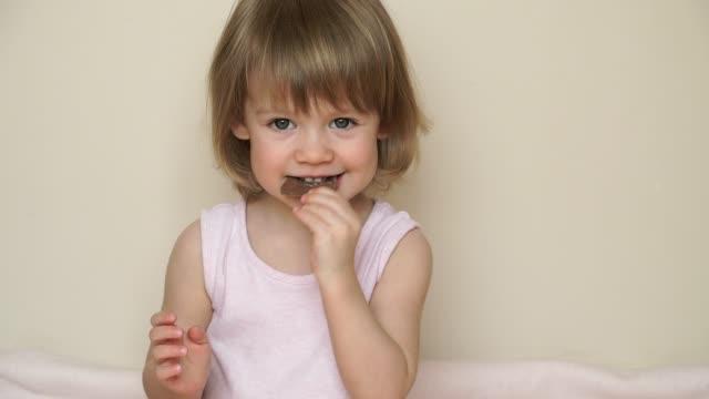 vídeos y material grabado en eventos de stock de el primer plano de la niña muerde con un gran pedazo de apetito de sabroso chocolate lechoso, come y sonríe - niñas bebés