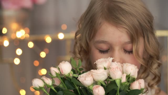 Close up of little funny child girl with bouquet of pink roses looks at camera, laughs, plays fool and smells flowers