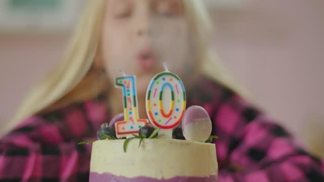 vídeos de stock, filmes e b-roll de feche acima de menina soprando velas coloridas com o número 10 no bolo de aniversário em câmera lenta. garota de 10 anos comemora aniversário. - data especial