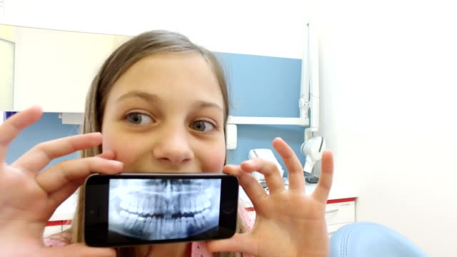 Close up of little girl holding smartphone with photo of dental x-ray video