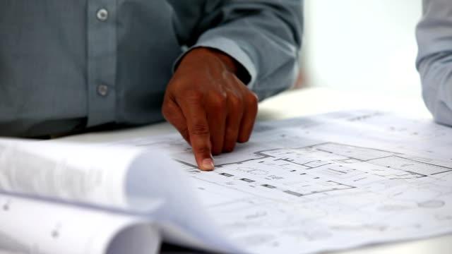 Gros plan de l'architecte mâle montrant un plan - Vidéo