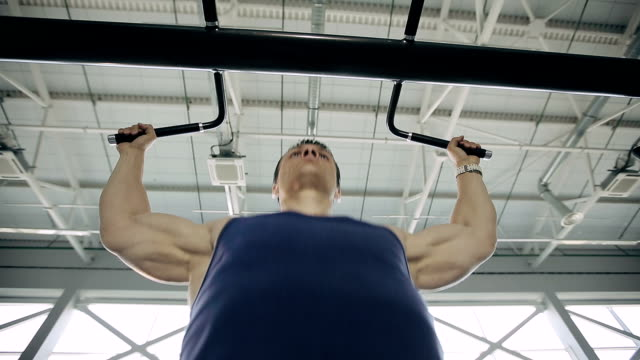 Close up of male bodybuilder pulling up in a gym video