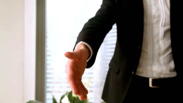 Close up of male businessman hand reached out for handshake video