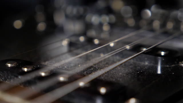 Close up of male fingers touching strings of a musical instrument. Chords being strummed and vibrating. Hand of man practicing to play on electric guitar in studio. Music performance. Slow motion