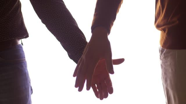 närbild på manliga homosexuella par hålla händerna - hålla handen bildbanksvideor och videomaterial från bakom kulisserna