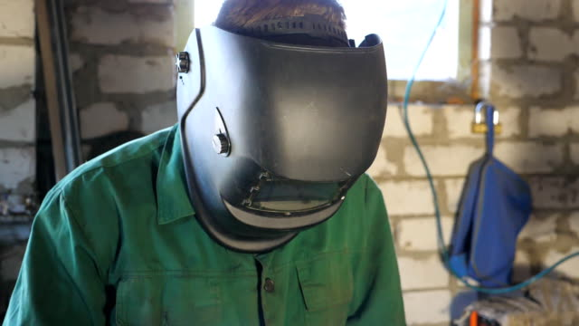 close up of male mechanic doing his work using protective mask. man in workwear works in garage or workshop. guy wears welding mask for his safety. hard work concept. slow motion - elektroda filmów i materiałów b-roll